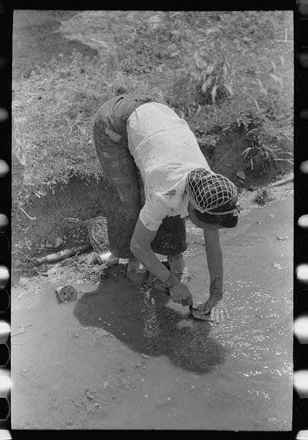 Washing off the plastering trowel in the irrigation ditch, Chamisal, New Mexico