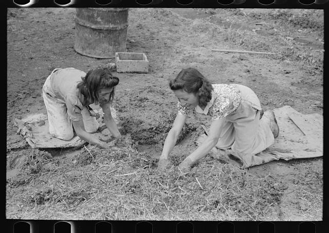 Spanish-American girls mixing adobe plaster with their hands, Chamisal, New Mexico