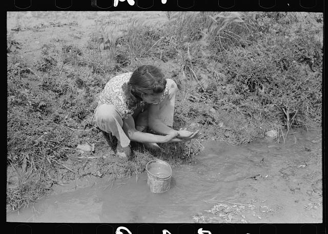 Spanish-American washing in irrigation ditch, Chamisal, New Mexico