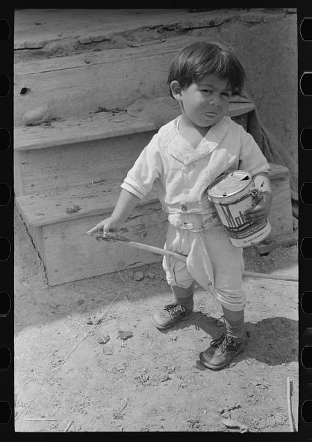 Spanish-American boy playing horse, Chamisal, New Mexico