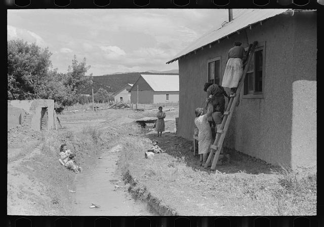 Plastering adobe house and washing near irrigation ditch, Chamisal, New Mexico