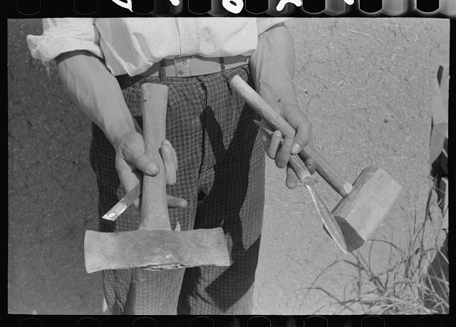 Handmade tools of Spanish-American farmer at Chamisal, New Mexico. The axe was made by welding two automobile spring leaves together and then sharpening; the dagger was filed down from a piece of automobile spring leaf and inserted in the bone handle. Chamisal, New Mexico