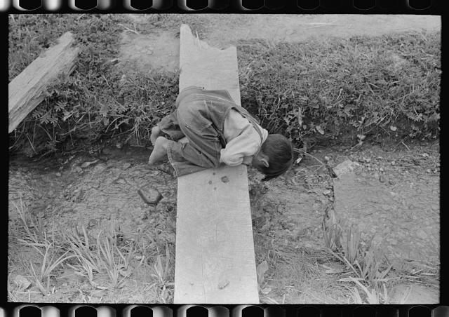 [Untitled photo, possibly related to: Spanish-American boy playing in irrigation ditch, Chamisal, New Mexico]