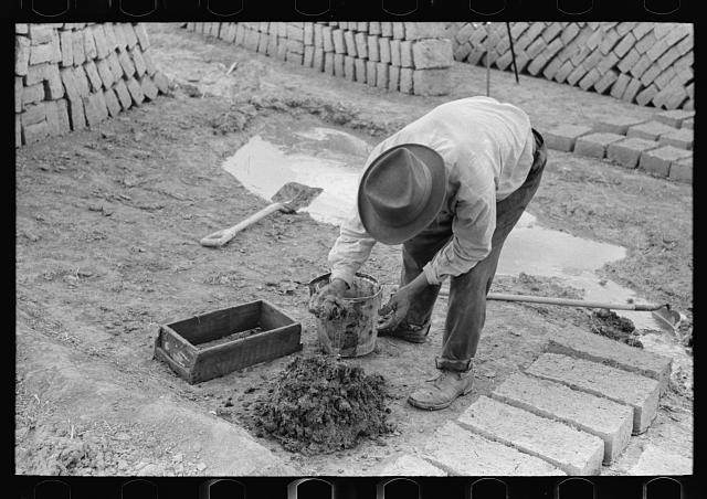 Adding water to adobe mixture for making bricks, Chamisal, New Mexico