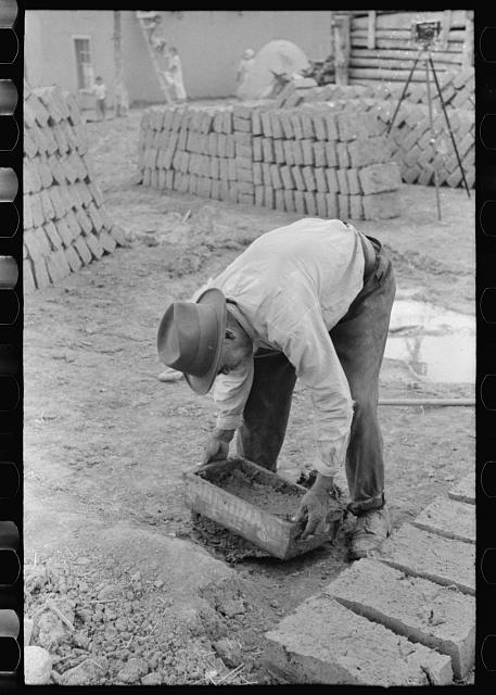 [Untitled photo, possibly related to: Mixing adobe for making bricks, Chamisal, New Mexico]