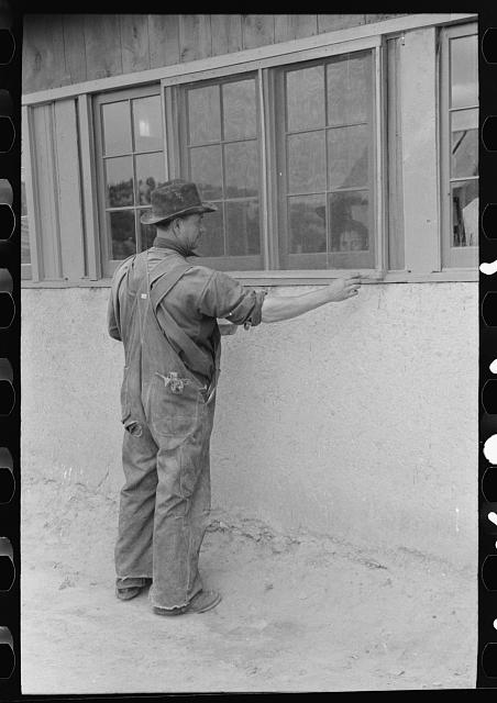 Spanish-American farmer painting window frames on his house. Spanish-American are proud of their houses. They are kept in excellent repair. Chamisal, New Mexico