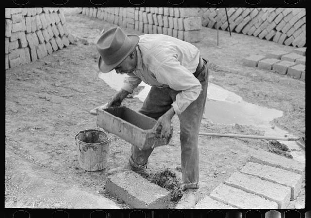 Spanish-American removing form shaped adobe brick. The adobe brick is next dried by the sun. Chamisal, New Mexico