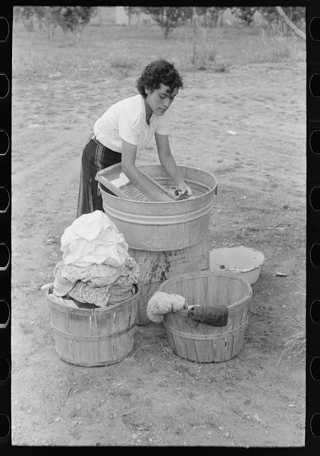 Daughter of Spanish-American farmer washing, Chamisal, New Mexico