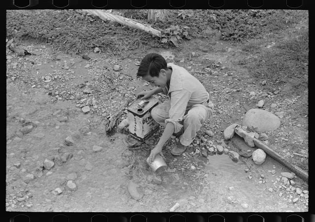 A Spanish-American boy dipping water from irrigating ditch. Water will be used in house for cooking, drinking, etc. Chamisal, New Mexico