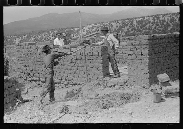 Plaster for adobe bricks to be used in building house is made from dirt dug in the front yard, Penasco, New Mexico
