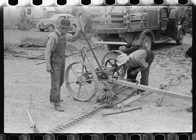 Spanish-American men looking over a mower, Chamisal, New Mexico