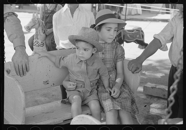 Spanish-American children waiting for a ride on the merry-go-round, Fiesta, Taos, New Mexico