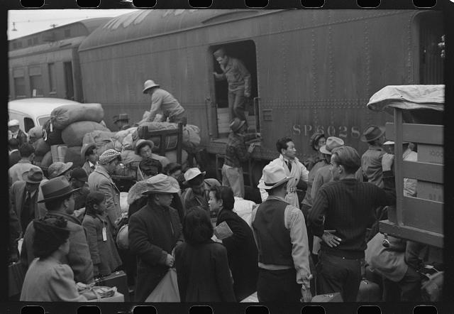 Los Angeles, California. The evacuation of the Japanese-Americans from West Coast areas under U.S. Army war emergency order. Japanese-Americans going to camp at Owens Valley gather around baggage car at the old Santa Fe Station