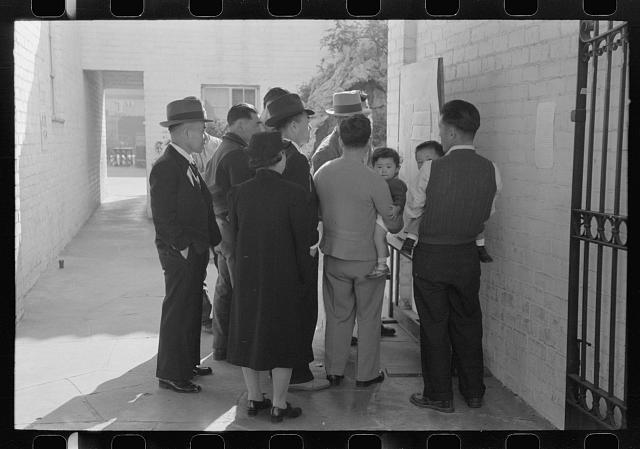 Los Angeles, California. Japanese-American evacuation from West Coast areas under U.S. Army war emergency order. Reading evacuation orders on bulletin board at Maryknoll mission