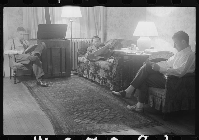 Washington, D.C. The room of a government clerk(?), showing three young men reading and listening to a radio in the evening