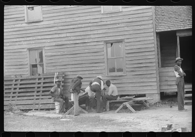 Migratory agricultural workers playing cards while waiting for their truck to arrive. They are leaving today for another job at Onley, Virginia. Near Belcross, North Carolina