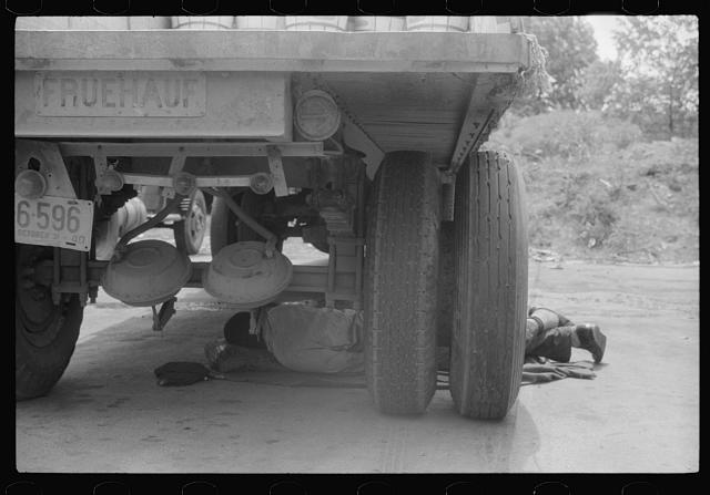 Negro driver asleep under a truck. There are no sleeping accomodations for Negroes at this service station. On U.S. 1