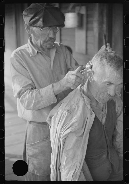 "[Untitled photo, possibly related to: Miners often give haircuts on front porch. The ""Patch,"" Chaplin, West Virginia]"