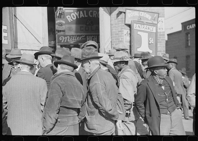Spectators listening to patent medicine salesman who has his stand outside tobacco warehouse during tobacco auction sales. Durham, North Carolina
