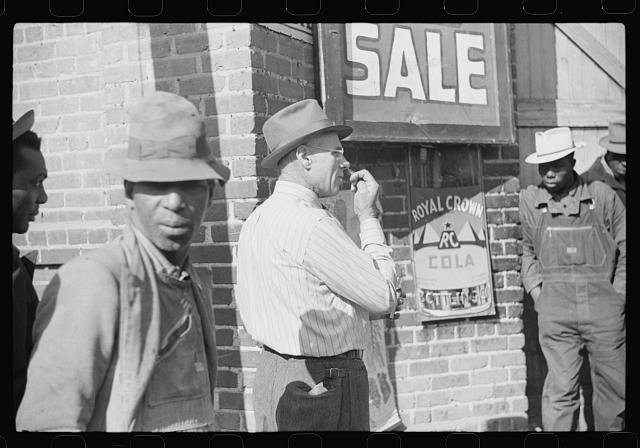 [Untitled photo, possibly related to: Patent medicine salesman demonstrating his wares to farmers outside warehouse during tobacco auction sale. Durham, North Carolina]