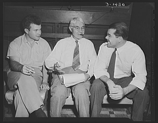 "Carl Sandburg famous for his lusty humor, is telling characteristic anecdote to Guy Bolte, motion picture director, on his left, and Phillip Martin, film editor, on his right. This photograph was made while Mr. Sandburg was working on the commentary for ""Bomber,"" national defense motion picture just completed by the Office for Emergency Management (OEM) film unit"