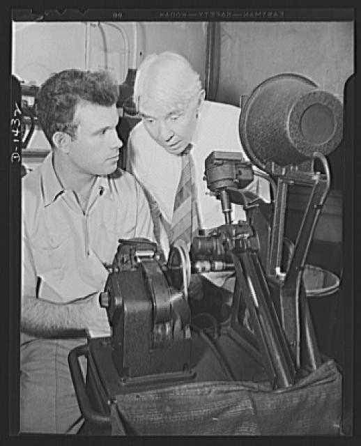 "Poet and historian turns to films. Carl Sandburg, famous poet and Pulitizer prize winning historian has turned movie maker. He has just written the commentary for ""Bomber,"" national defense motion picture produced by the Office of Emergency Management (OEM) film unit.  He is shown here in the cutting room with Phillip Martin, film editor and technical supervisor of the film unit"