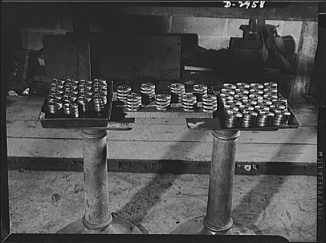 Subcontracting (Braden and Van Fossen Works). These are lock nuts for Navy destroyer, cut from solid steel bars at the Braden and Van Fossen Works, Staunton, Virginia. A special set of dies, jigs and furring tools were built for this job, which was filled in half the time allotted by the prime contractor. The nuts in the center are already finished, the others await merely furring of the edges