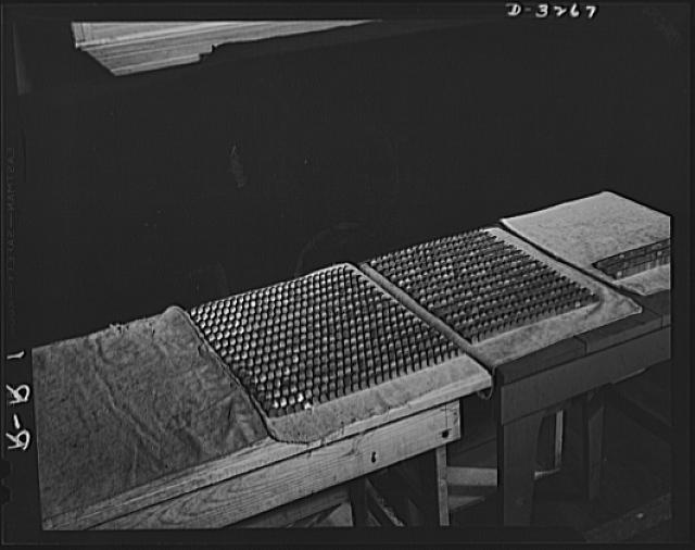 Oil burners to machine gun parts. Not marbles or thimbles, but row upon row of completed machine gun parts, today's production of an oil-burner factory in upper New York State. Manufacture of these small parts requires top skill, for tolerance of 1/10,000 of an inch is demanded by U.S. ordnance officers. Reif-Rexoil Company, Buffalo, New York