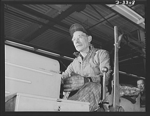 "In a big automobile plant changing over to production of shells, this ""Cat Skinner"" (tractor operator) was kept busy for some time pulling, turning and bulldozing machines into new location. Oldsmobile, Lansing, Michigan"