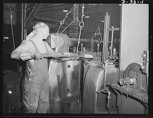 The forging of a shell for the Army involves operations that skilled men, working with highly developed power equipment, take in stride. Both men and machines were quickly converted from peacetime workers in an automobile plant to wartime producers for America's arsenal of democracy. Oldsmobile, Lansing, Michigan