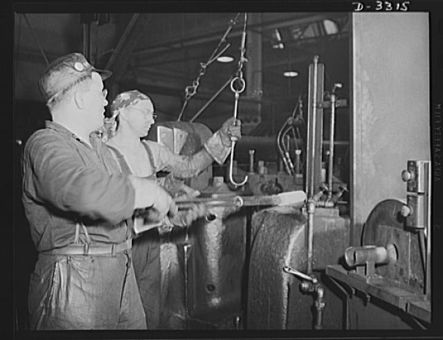 A number of forging operations are required to produce a shell for the Army. Experienced auto plant workers do this work as efficiently as they did parts for the family car. Oldsmobile, Lansing, Michigan
