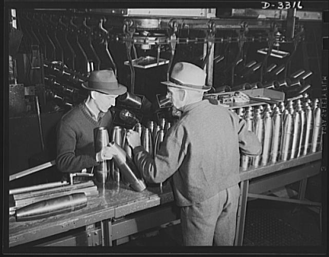 Accurate workmanship is required to make perfectly uniform shells for the Army. Inspectors are on the alert to reject those which fail to meet requirements. Oldsmobile, Lansing, Michigan