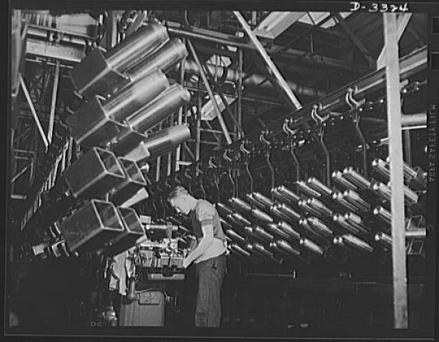 It's hard to recognize the production layout of a well-known auto plant in machine lines that win with wartime production. It's shells instead of auto parts now--but American industry can turn out the orders for war as well as for peace. Oldsmobile, Lansing, Michigan