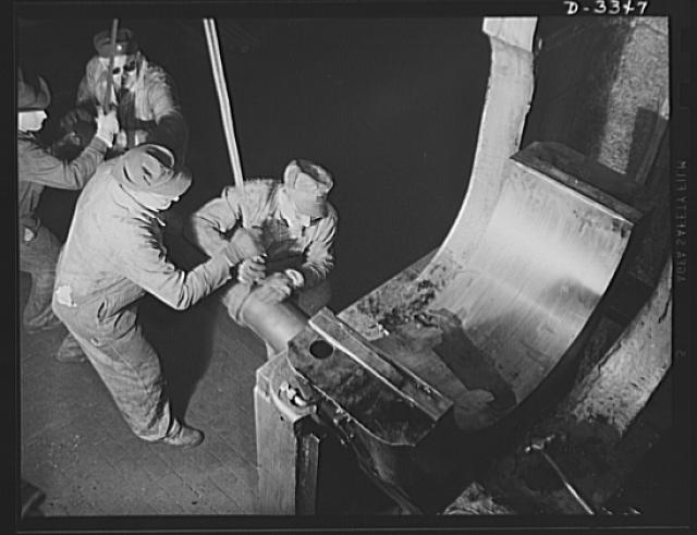 A bearing of a big forge hammer is removed for overhauling as the maker of a popular American car switches over to production of machine guns for the Air Force. Every machine in the plant must be in perfect condition for big orders in the months to come. Oldsmobile, Lansing, Michigan