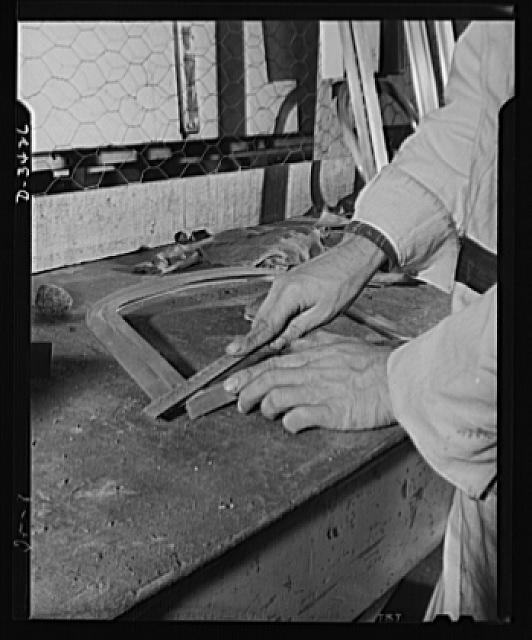 Conversion. Metal screens to bomber windows. Finishing a navigator window frame for a bombing plane in the plant of an Eastern manufacturer of metal door and window screens