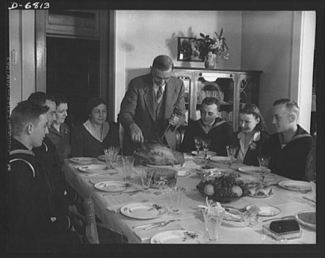 Thanksgiving, 1942. Turkey, pumpkin pie, cranberry sauce, sweet potatoes--nothing is too good for Uncle Sam's fighting nephews when they come home to Silver Spring, Maryland. The four Coast Guardsmen, eyes riveted on the juicy turkey, watch their father, Wayman Fincham, as he carves. Seated next to him is Mrs. Fincham and next to her is the wife of Fincham's eldest son, who is fighting overseas. Another daughter-in-law is seated between the two Coast Guardsmen at the right. The sixth and youngest of the Finchams is a Coast Guardsman in training