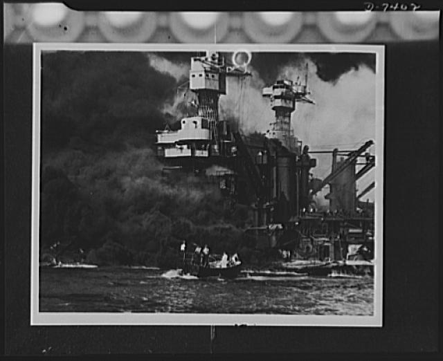 Pearl Harbor bombing. Seaman rescued. A small boat rescues a seaman from the 31,800 ton USS West Virginia burning in the foreground. Smoke rolling out amidships shows where the most extensive damage occurred. Note the two men in the superstructure. The USS Tennessee is inboard