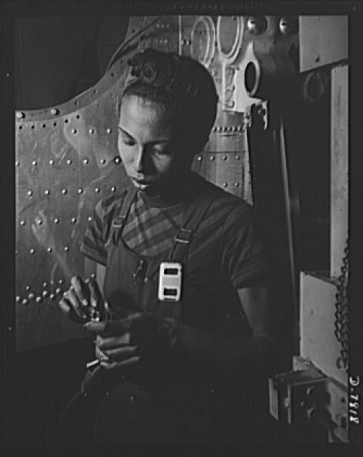"Production. B-17F heavy bombers. Negro girls are proving willing and capable aircraft workers. This girl works on wing jigs in the assembly of B-17F heavy bombers at the Long Beach, California, plant of Douglas Aircraft Company. Better known as the ""Flying Fortress,"" the B-17F is a later model B-17, which distinguished itself in action in the South Pacific, over Germany and elsewhere. It is a long range, high altitude, heavy bomber with a crew of seven to nine men and with armament sufficient to defend itself on daylight missions"
