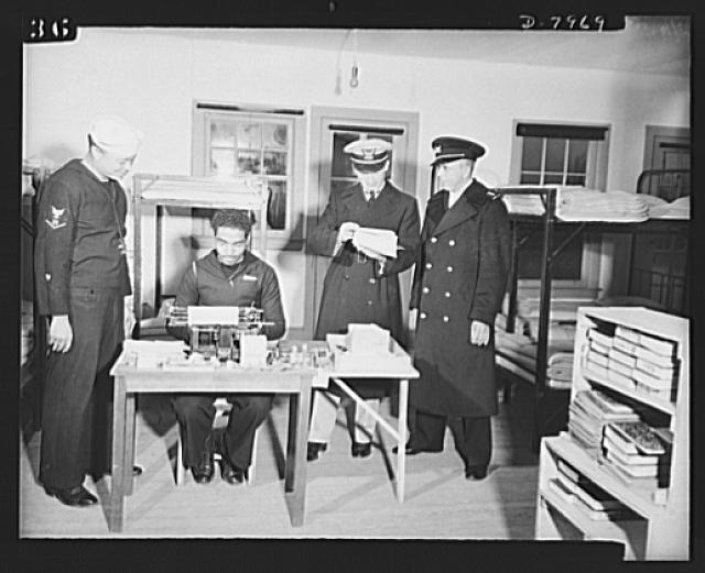 Manhattan Beach Coast Guard training station. Company Clerk Roy W. White (seated at typewriter) takes dictation from Coxswain and Company Commander Paul L. Perkins of Company 24, U.S. Coast Guard training station, Manhattan Beach. Also shown are Assistant Training Officer, Lieutenant E.A. Simpson and Boatswain Clarence Samuels
