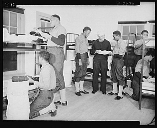 Manhattan Beach Coast Guard training station. Bag inspection in barracks of Company 24 at Mahattan Beach Coast Guard training station is a daily chore. Company Commander Paul L. Perkins is shown inspecting equipment of enlistees and showing new recruits how to roll equipment so that it can fit into the duffle bag