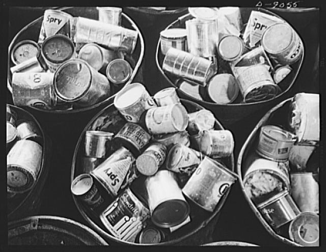 Conversion. Rendering of household fats. Cans of waste fats collected from America's kitchens come to a rendering plant in large steel drums. Note that the cans of various sizes and with or without covers, are mostly coffee and shortening cans now unavailable to many housewives. Any type of clean can may be used