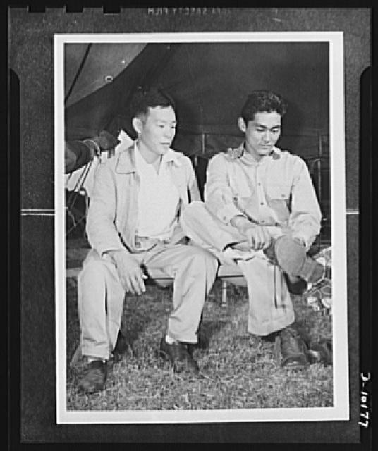 "Japanese-American volunteers. There's quite a difference between sneakers and a pair of heavy GI boots, Mitsuru Doi, eighteen, of Kauai, finds out. He was the first to put on the uniform of an American soldier. Looking on is a fellow inductee, Shuichi ""Pete"" Sakamoto, thirty-four, who before his induction was surveyor and civil engineer for the Lihue Plantation Company. Sakamoto, married, is the father of a two-year-old son"