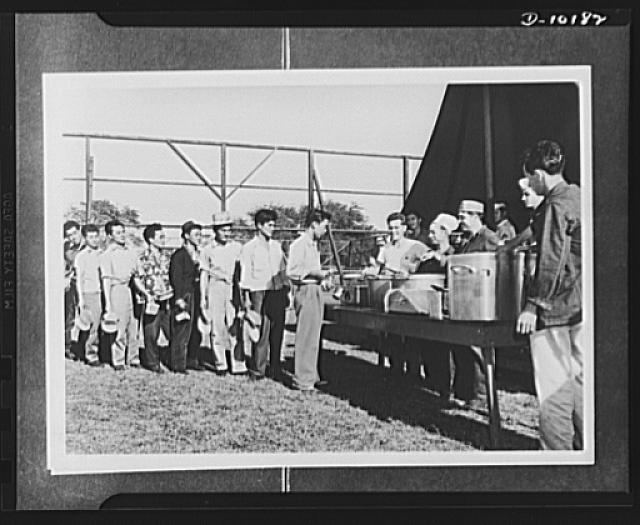 Japanese-American volunteers. A typical army scene--waiting in line for dinner. First of the territory's AJA [Americans of Japanese ancestry] volunteers to take their physical exams, these Kauai, Hawaii men were quartered in a provisional camp pending annoucement of results of final tests. Here they enthusiastically form their first chow line as dinner is served. A few of the volunteers started off right by going on KP (Kitchen Police) duty the first few hours in camp