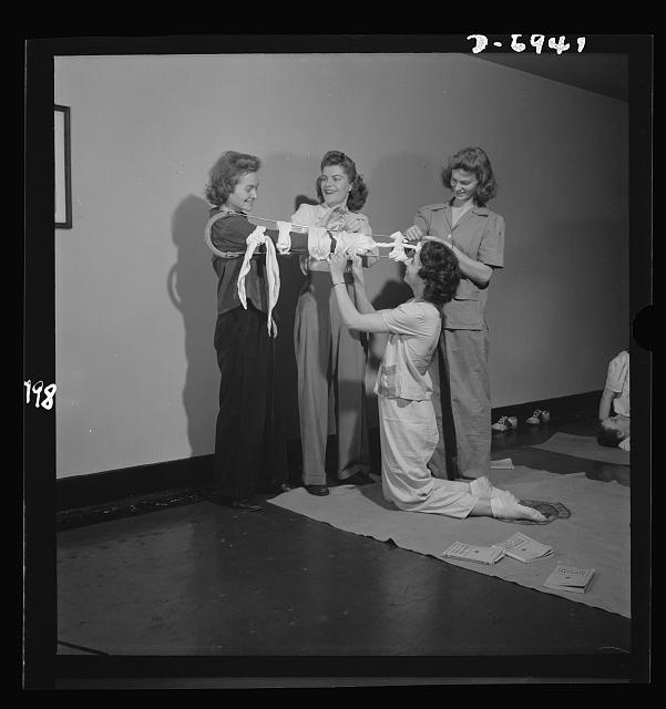 "Nurse training. Student nurses, like millions of other United States citizens, are today taking Red Cross First Aid courses, but with a difference. These students of nursing are taught not only to give first aid in case of air raids or other war or peacetime emergencies, but also how to deal with amateur first aiders. Here a group of young nurses adjust a traction splint on a fellow ""victim"""