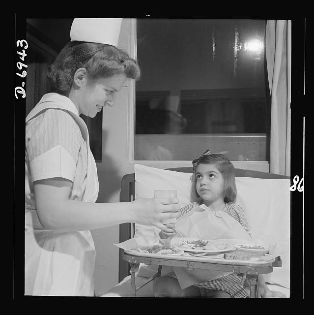 Nurse training. A convalescing youngster gets lunch with a smile from a student nurse