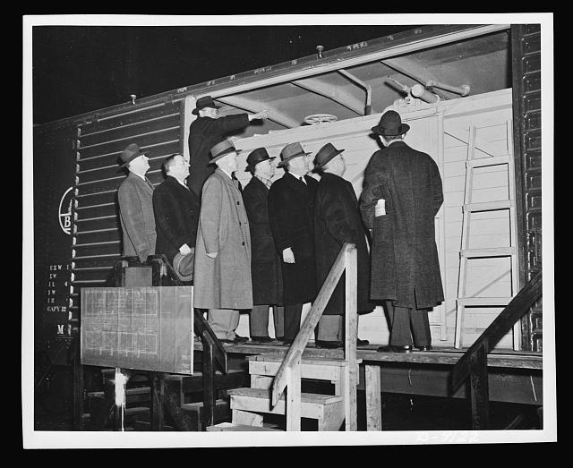Government and railroad officials inspect the new model boxcar petroleum carrier designed to help the oil shortage in the East. It is estimated by officials of the Office of Defense Transportation that one thousand such cars could add more than 15,000 barrels to the daily receipts of petroleum by rail in the East