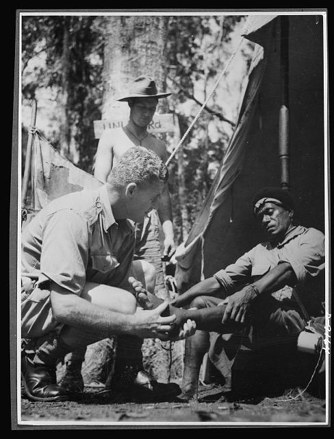 Natives aid Allied drive in New Guinea jungles. New Guinea natives receive the same medical attention as Allied troops, since their work is of vital aid to the Allied forces. Corporal McNicol, medical orderly at one of the forward outposts in the New Guinea jungle, attends one of the native carriers passing through the area