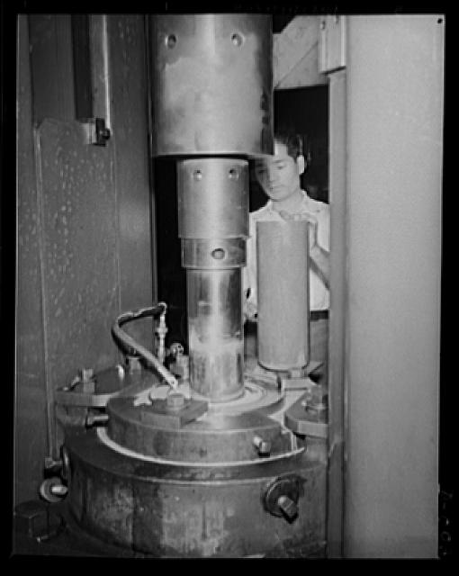 Cartridge drawing machine. Skilled worker drawing a five-inch cartridge case for the big anti-aircraft guns. The yard in which this work is performed is one of eleven Navy arsenals which are working at top speed to furnish ammunition needed for our two-ocean Navy