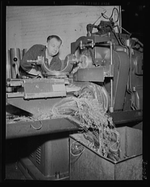 Brass shavings from cartridge cases. One of the last processes in making anti-aircraft cartridges is machining the head of the case. This worker in an eastern Navy yard is one of thousands who are producing ammunition for the expanded Navy war program