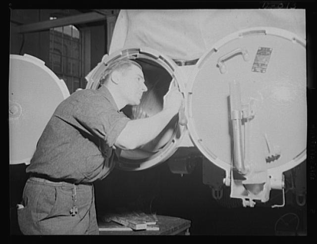 The open door to a torpedo. Close work fitting a torpedo tube door in an eastern Navy yard arsenal, one of eleven now working at top speed for the expanded war program